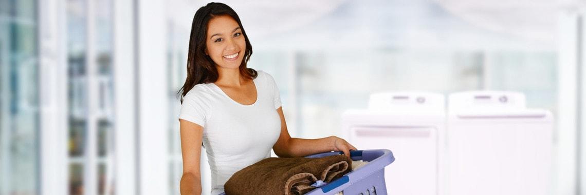 Eine frau mit Ihrer Wäsche aus Ihrem Wärmepumpentrockner.