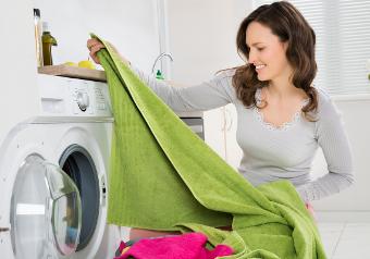 Hier sehen Sie eine Frau die Wäsche aus einem Trockner holt.
